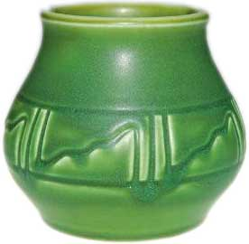 Squat Z line 3 3/4 inch vase encircled with a Native American style design and covered with a good mat green glaze in 1904