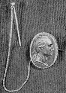 ILLUSTRATION I: A Berlin Casting Brooch: This brooch, with pin and chain, probably belonged originally to Mrs. Tobias Lear, niece of Mrs. Washington. It has a lock of the General's hair enclosed in the back. Size 14/16 by 10/16 inches.