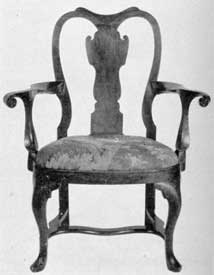 A Philadelphia Armchair: This is a typical example of the fine work done by Philadelphia cabinetmakers. Made of walnut, the shaping of the seat, back, legs, and bold curve of the arms show the Queen Anne style in its most elaborate manner.