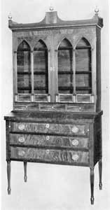 Illustration V: A Sheraton Secretary from Salem: The reeding of the legs, use of curly-maple veneer for the drawer fronts, and reeded pilasters framing the glasses of the doors, are evidences of the skill possessed by Salem craftsmen in the first decade of the 19th Century.