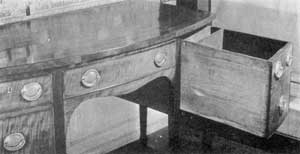 ILLUSTRATION III: A Sideboard with Concealed Space: The deep drawer at the right has been pulled out to show the false back and additional space behind it. This might readily go unnoticed and provided a good hiding place for pieces of silver.