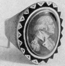 ILLUSTRATION VI: A St. Memin Ring: This artist engraved two miniature portraits of Washington. This is the one in uniform. The other was a profile, laureated. Both were colored to simulate painted miniatures. Ring, probably the work of John Baptiste Dumoutet, Philadelphia goldsmith.Size 10/16 by 8/16 inches.