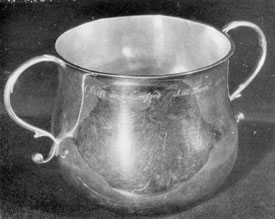 "Illustration V: Caudle Cup by Quintard: Just under the rim is the inscription, ""The Gift of Jonathan Gold to the Church of Christ in Stamford An Dom 1730."" All that is known of the donor is that he was a sergeant in the militia, lived as a youth in New Haven and later removed to Stamford. About 1800, descendants changed the spelling their surname to Gould. This cup has long been used for baptisms. It is three and one-half inches high, four in diameter and has a spread of six and one-half inches across the handle."