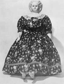 Illustration II: Doll with Composition Head: Made by Ludwig Greiner who produced these dolls from 1858 to 1878. This example with full skirted flowered dress portrays the styles of the mid-19th Century.