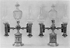 English Regency Period Lamps: The lighting fuel used in such lamps equipped with Argand burners was generally a refined sperm oil. This pair have Wedgwood jasper-ware bases, elaborate Waterford cut-glass decorative finials, and carefully blown glass chimneys so shaped as to make them the best source of artificial lighting possible.