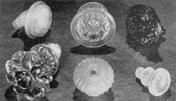 Fragments from Sandwich: Upper row, left to right: Conventionalized floral designs in opalescent, canary-yellow, and dark-blue glass. Lower row: Large rosette knob with glass screw shank (not found at Sandwich but attributed to it), broken, ribbed mushroom knob, and small knob with screcw-threaded shank. The last two are of clear glass that has become frosted from being buried in the ground.