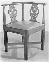 Illustration X: A semi-sophisticated chair of cherry with pierced backsplat. In the Chippendale manner, it was made circa 1765-1785. The rectangular cross stretchers and ornamental brackets beneath the joining of seat frame and legs are unusual. The curved arms and comb are restrained in outline.