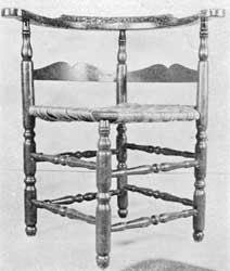 Illustration II: A well-proportioned country chair, with original Cape Cod brown paint, circa 1780-1800. Made of maple with hickory back-slats. The turnings of legs and all eight stretchers are vigorous. The Cupid's bow outline of upper edge of back-slat differs from that of ladder-back chairs of the period.