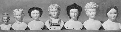 Illustration V: Imported Doll Heads of the 19th Century: From left to right the materials used are, Meissen, Parian ware, china, Parian, china, bisque, and china. The fifth head depicts the Empress Eugenie; the seventh, Jenny Lind.