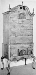 New England Maple Highboy: With bonnet top, fan-carved drawer fronts, finials and scalloped apron, this is a typical example of the design during the latter part of the period.