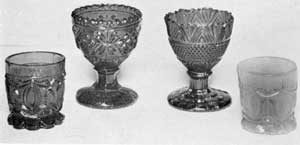 Night Nips and Egg Cups: Of two small rum cups in the foreground, that at the left, in emerald green, has a conventional design with stippling; while that at the right, in pale blue, has the same design without stippling. The egg cups are both of deep cobalt blue. That at the left has a design of leafage and diamond shapes; that at the right, with serrated upper edge, is a combination of stippling and diagonal ribbing in design.