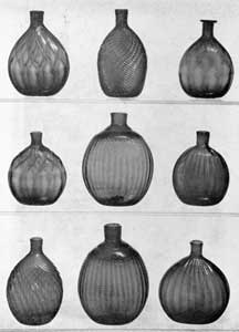 "Illustration I: Nine Ohio Blown Flasks: All are about one-half pint capacity. Top row, left, typical Zanesville flask of ogival, sometimes called quilted design, in amber glass; center, flask patterned twice in the mold showing broken swirl design, very heavy, that produced the ""popcorn kernel"" effect; right, this is unusual because of its flanged lip. Center row, left, another Zanesville quilted flask of deep amber-colored glass; center, Pitkin-type flask in deep anther glass; right, flask with vertical expanded ribbing in reddish ember glass. Bottom row, left, flask with expanded swirled ribbing in dark amber glass; center, Pitkin-type flask in deep amber glass; and right, flask with vertical expanded ribbing in reddish amber glass."