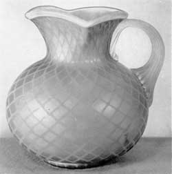 Pitcher of Mother-of-Pearl Glass: In color, this piece is a brilliant pastel blue which is set off by the lattice of the exterior, the translucent handle, and the rim at the mouth.