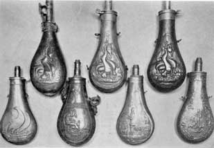 "Plate V – Seven Typical Flasks: Top row, three with same embossed decoration of hanging game. At the left, a leather flask for bird shot; center, copper flask marked ""James Dixon & Sons"" immediately beneath the decoration; right, a copy of the same design marked on the charger, ""American Flask & Cap Company."" Bottom row; left to right, an unmarked American army flask; an English flask with Grecian decoration; and two English sporting flasks with hunting scenes in which the men wear top hats."