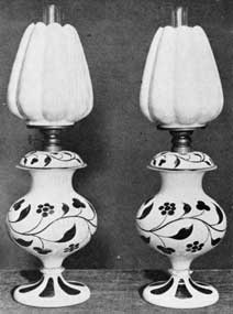 Handsome Sandwich Lamps: Made with opaque white and rose-colored overlay glass bases and shades of a delicate pink glass with translucent white on the outside. Lamps such as these date from the time when kerosene had replaced other fuels for lighting purposes.