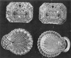 Illustration III - Pipes-of-Pan Trays and Two Shell Dishes: These pairs of trays are the only large Lacy Sandwich pieces with a design bearing anything like a human form. Dimensions 8 inches long. The two shell dishes, below, should be included among the choicest examples of Lacy glass. The dish at the left is in the Hairpin pattern. Dimensions, 9.5 by 8 inches. The dish at the right has the Peacock-Eye border. The open handle made this a difficult piece to produce. Dimensions, 9.5 by 7.75 inches.