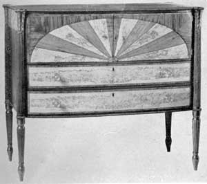 Illustration III: Sideboard by William Hook: The piece, with door fronts inlaid in an unusual half-oval pattern, was made as a wedding present, 1808-09, for his sister Hannah Hook Folsom. The reeded legs, with waterleaf capitals, are characteristic of Salem work.