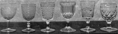 Six American Pattern Glass Goblets: From left to right the patterns are: Grape, collectible only in goblets; Diamond cut with Leaf; Paneled Daisy; Prism; Strawberry and Currant; and Honeycomb.