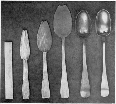 "From Strip of Metal to Finished Spoon: From left to right, these six stages show the principal steps followed by Early American silversmiths in spoonmaking. It started with the strip of rolled silver at the left. Next, shaping of the bowl and handle was started and continued through three stages. Then with a punch and die the bowl was ""struck up"" that is, made concave and the handle was given its proper curve. After this, the edges were smoothed with files and the spoon carefully polished with burnishing tools. This set of steps follows the design of a Paul Revere spoon made about 1770."