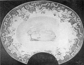 3. Staffordshire shaving basin with a black on white transfer scene and a border of grapes, leaves and geometrical motifs. English, 1840-50.
