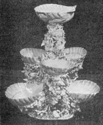 Illustration V: Sweetmeat Stand: This elaborate piece consists of three tiers of scallop shells supported by clusters of applied coral, small shells and seaweeds.