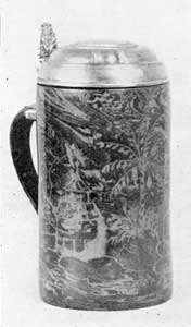 Illustration II: Tankard of Boettger: Porcelain: This unique piece, formerly in the Hearst collection, was made circa 1710. It has silver gilt mounting and is unmarked. It was copied from a tin model. The decoration was produced by incrusting of lighter shade on a darker background. It is eight inches tall.