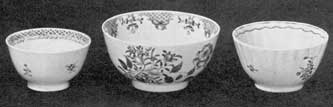 Two Cups and a Small Bowl: The bowl with more extensive decoration and in clear colors dates from 1767. The cup at the left, decorated all in a dull pink, is about 1815; that at the right, done in various colors with a pink border, is more brilliant than the other cup. Notice the sparcity of design on the cups compared with the earlier bowl.