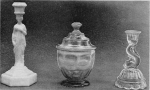 1. Three pieces of American glass that show exceptionally fine detail. Left to right: Opaque white candlestick in the shape of a caryatid, probably made by the Boston Glass Company. Fiery opalescent sugar bowl in the Ashburton pattern, made by the New England Glass Company. Petticoat dolphin candlestick with opalescent rim, maker unknown.
