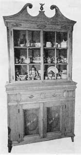 Architecturally Designed Dish Cupboard, Circa 1800: Of pine with finely carved sunbursts decorating door fronts and cornice, this piece was made near Nyack, New York. In all its details it is characteristic of work done in the upper Hackensack Valley by craftsmen of Netherlands descent.