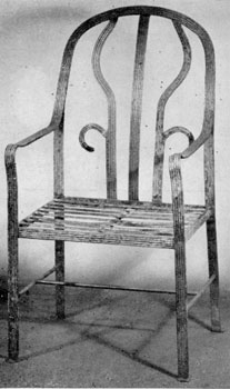 An Armchair in Iron: In design, this is probably a Chippendale-Hepplewhite transition piece. The front of the legs and back are nicely reeded and it has small, simple paw feet.