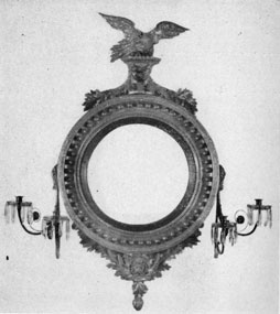 Bull's Eye Mirror Sconce: A handsomely carved and gilded piece made in New York about 1800, the circular convex mirror reflected the light of the four candles placed in the sconce arm at either side.