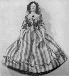 From the Second Quarter of the 19th Century: This doll has a papier-mâché head, a kid body, and wooden arms and legs. Its total height is 9 1/2 inches. The dress is of green and cream striped satin.