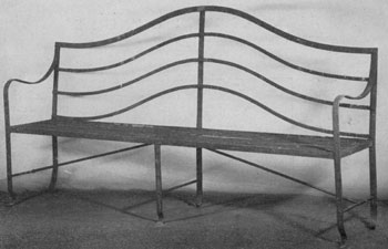 A Garden Bench in Hepplewhite Style: The cresting members of the back, the use of reeding and the small paw feet are its decorative features.
