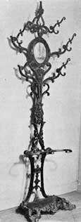 Hat Rack of Cast-Iron: Like those of wood this is complete with central mirror. The design combines conventional scales with touches of Gothic Revival. Such pieces of furniture are less seldom found than chairs and benches but were popular in their time.