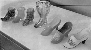 Illustration IV: Shoes and Slippers in Glass: At the left are three shoes in colored case glass with applied leaves in small festoons. The three slippers at the right are of opaque glass, two of which have hand painted decoration.