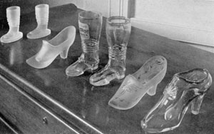 Illustration VI: More Boots and Slippers: Of the two high boots in the center, that at left has a view of Hamburg at the top of the leg. The slippers at the right are rarities as are the smaller frosted boots at the extreme left.
