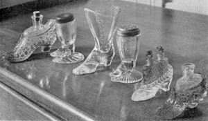 Illustration VIII: Other Shoe and Slipper Designs: The salt and pepper shakers in the center have perforated pewter tops. The slippers have the original perfume bottles for which they were made as holders.