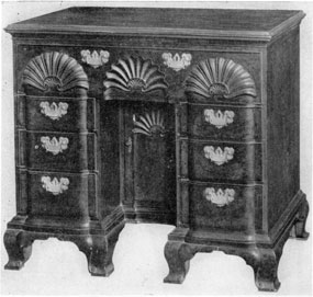 A Knee Hole Dressing Table: Made by John Goddard the famous cabinetmaker of Newport, Rhode Island, this block-front mahogany piece was adapted from Chippendale designs. The cupboard at the rear of the knee hole was used as storage of the owner's wig block. Many of these pieces had the top drawer hinged and the lower side fitted for writing. Then it was also used as a desk.