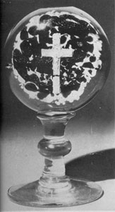 Millville Paperweight Mounted On Goblet-like Base: Here the central figure is a sulphide crucifix and the background is of mottled green and brown glass. This was originally made as a flat paperweight and the footed base was developed later.