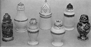 Of Leeds and Staffordshire Ware: The five pepper pots in the center are Leeds. They are of cream-white pottery with simple decoration in blue or green. The two at the extreme left and right are Staffordshire with deep-blue transfer decoration.