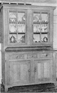 Pennsylvania Country Dish Cupboard: Made of pine approximately 1800 to 1825, decoration was gained by use of reeding and star and circle carving of face of the two larger drawers. Restoration showed that it was originally painted in Ammish blue.