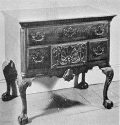 A Philadelphia Lowboy: Made in walnut, the ornamentation, proportions, and workmanship of this piece is representative of the best Philadelphia craftsmanship. The carved leafage on the cabriole legs and the concaved shell and volutes of the central small drawer are particularly well executed. It was made for a member of the Franklin family.