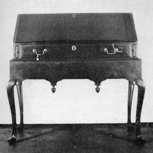 Illustration II: Queen Anne Desk on Frame: Made about 1720, the writing lid folds outward and rests on sliding bracket supports. The finials of the apron are reminiscent of the earlier period of William and Mary.