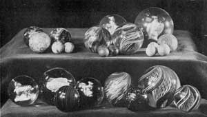 Typical Marbles That Collectors Seek: Upper row at the left, three large and two small ones of pottery; in the center, three glass shooters and small ones of clay; and right, a large glass one with sulphide center in shape of an eagle with four of clay with colored stripes. Lower row, left to right, three with sulphide centers, two of enamels and one of a fish. In front of them, one of slag glass. Next, one with opaque and irregularly swirled center. To the right and in center of this, a marble of amber glass with embedded metallic flecks. At the extreme right, two sizes of clear glass marbles with swirled center of colored threads. The technique employed in making these was approximately that used in paperweights of similar decorative design.