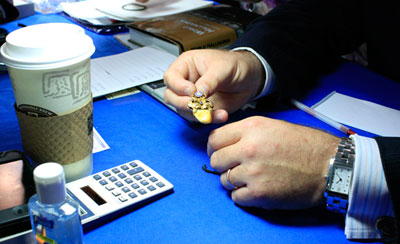 At the Jewelry table, Adam Patrick of A La Vielle Russie, Inc. examines an Elks fob from the early 20th century. The piece is made of 14k yellow gold, includes a diamond and a sapphire, and holds an elk's tooth. It was appraised at $750 to $800.