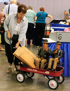 A guest with Laurel and Hardy figures waits to learn how her items will be sorted. This will determine which table she brings them to once inside the Roadshow set.