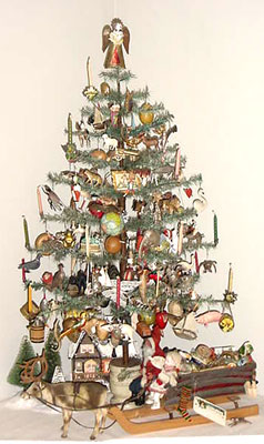 "40"" tall antique feather tree decorated with German ""Dresden"" ornaments.  The tree has built-in candle holders and has an early round wooden base.  The ornaments are all embossed cardboard dating ca. 1870 thru 1910."