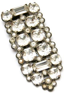 This Eisenberg clear crystal dress clip from 1940 boasts baguette, round, and cushion-cut stones set in a pot-metal back.