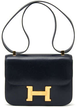 An Hermes Navy Leather Constance, 1976, with matching shoulder strap, open pocket at back, with a flap closure snapping at H, gold hardware, blind stamp circle F. Stamped: Hermes.