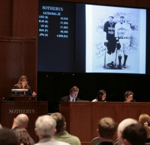 Dunbar (left) in action at Sotheby's, auctioning a photo signed by Babe Ruth and Lou Gehrig.